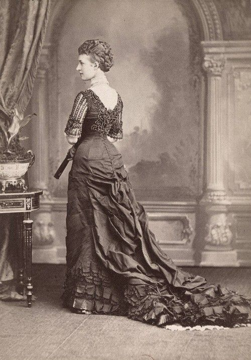 Queen Alexandra facing away from the camera, showcasing her back and the cascade of fabric bustle leading to a lengthy train, ca 1877
