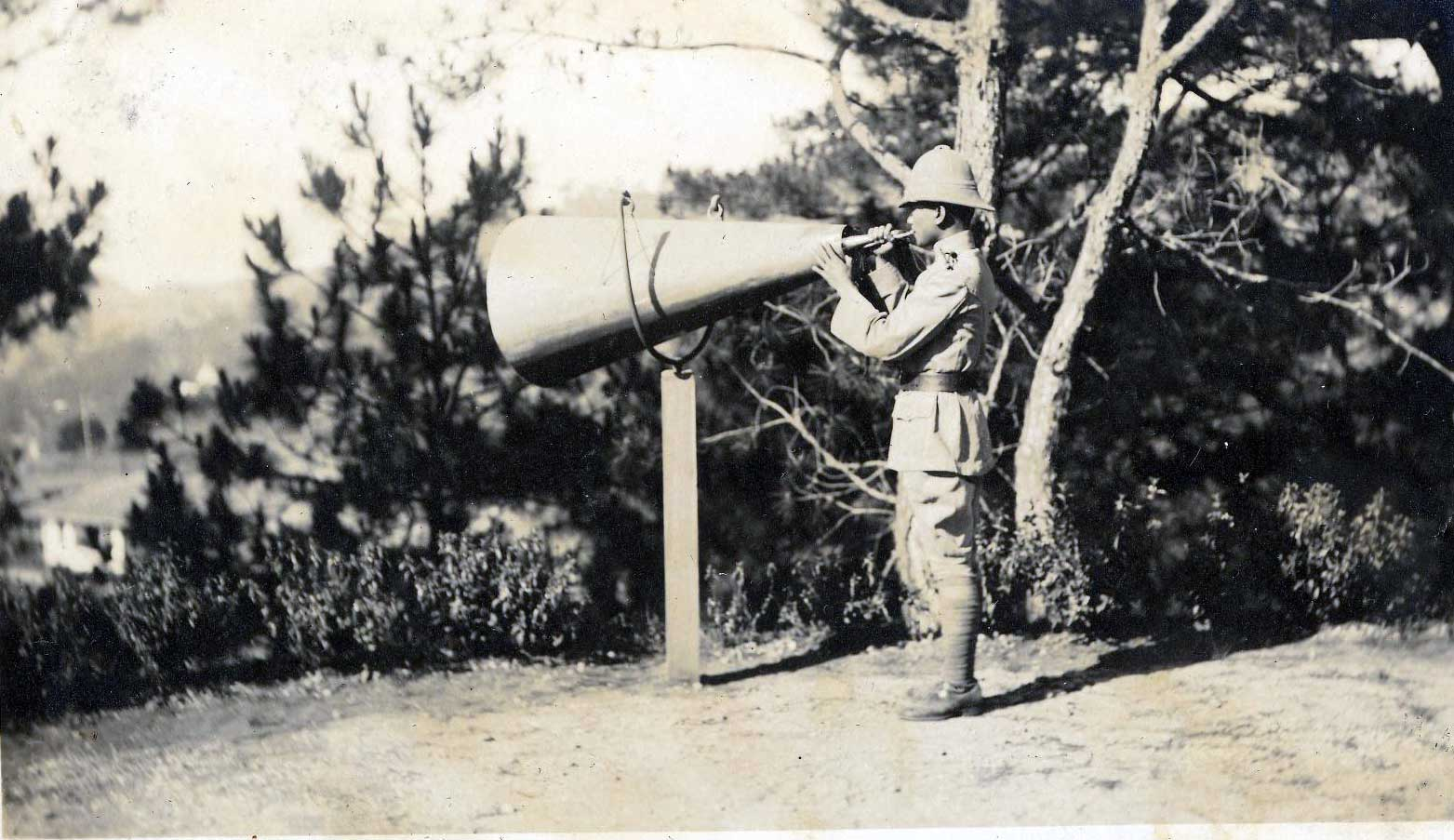 Featured photograph of a Filipino soldier blowing a horn to call for formation, from the University of Michigan Special Collections Library.
