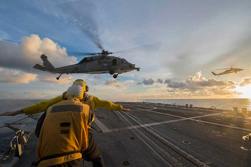 """Sailors signal to an MH-60S Sea Hawk helicopter attached to the """"Golden Falcons"""" of Helicopter Sea Combat Squadron (HSC) 12 as it hovers over the flight deck of the Arleigh-Burke-class guided-missile destroyer USS McCampbel in the South China Sea."""